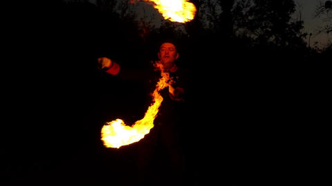 Circus Man Turns Two Lit Flambeaux Around. They Look Magic at Night in Slo-Mo Footage