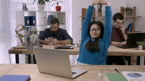 Casual businesswoman stretching at desk in office Footage