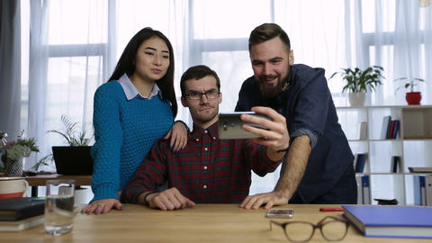 Casual colleagues taking self-portrait in office Footage
