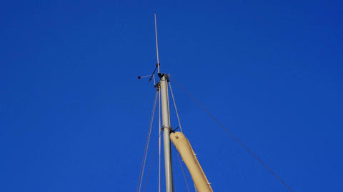 Sailing boat main mast close-up. Wind blowing and turning windex against clear Footage