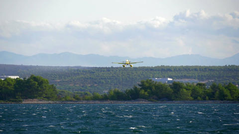 Fire fighter airplane flying over small island to get some water for forest Footage