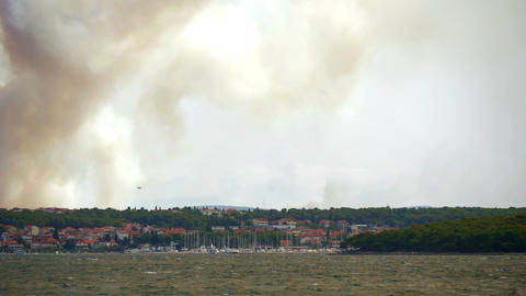 Fire fighting airplanes extinguishing forest fire at Croatian coastline next to Footage