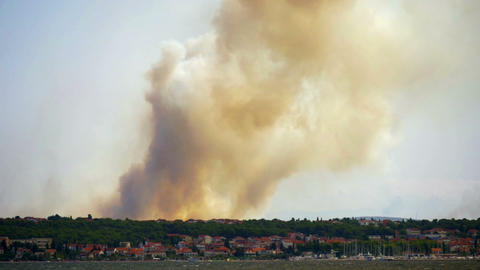 Forest fire with lots of smoke at Croatian coastline shot from island Pasman. Footage