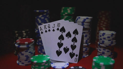 Royal flush on cards and poker chips on red casino table Footage