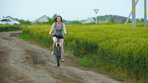 healthy lifestyle woman riding a bike on rural road Footage