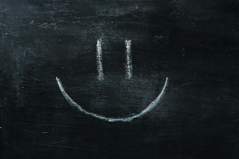 White happy smiley face on a blackboard background, closeup Fotografía