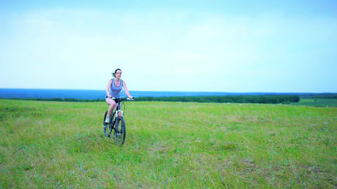 Girl cycling through a field in summer Footage
