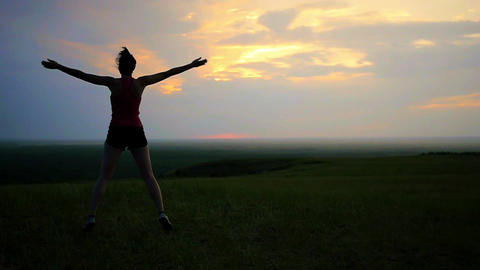 athlete warming up doing jumping exercises running on a sunset background Footage