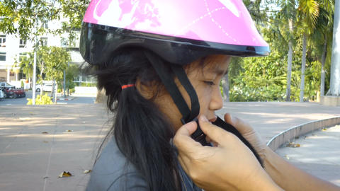 Mother hands wearing safty helmet to cute Asian little girl Image