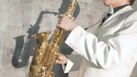 A musician in a white suit plays the saxophone. He performs in a nightclub Footage