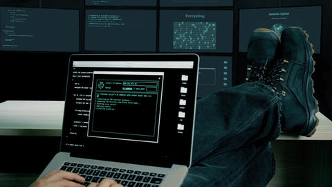 Hacker feet up to table. Hacker with laptop coding exploit to crack code. Man in Live Action