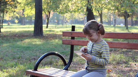 little girl play with tablet pc in park Live Action