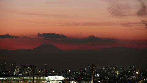 Silhouette of Mt.Fuji and cloudscape behind city lights Footage