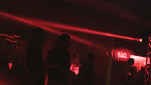 Camera Shows Dancing Clubbers Silhouettes under Red Light Footage