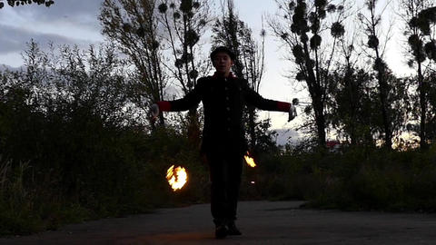 Juggler Twists Two Balls of Fire on Metal Cords Like Windmill Wings in Slo-Mo Footage
