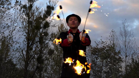 Fire Man Twists Two Lit Fans Around Himself Outdoors in Slo-Mo in Autumn Footage
