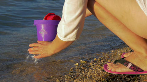 mother washing childrens toys with hands in sea after nice time at sea beach in Footage