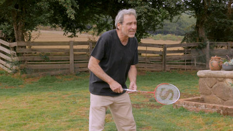 Active senior man playing badminton missing the shuttlecock Footage