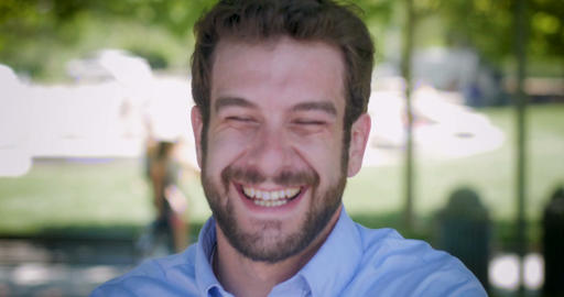 Attractive millennial man in 30s with beard laughing out loud during the day Footage