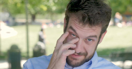 A man in his early 30s with a short beard trying to get something out of his eye Footage