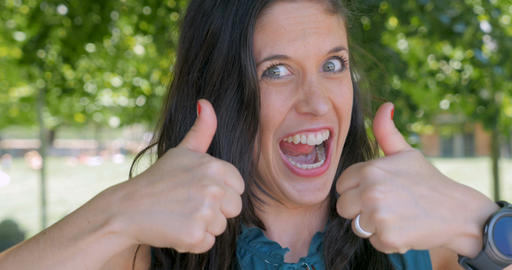 Enthusiastic attractive woman in early 30s giving two thumbs up agreeing with Footage
