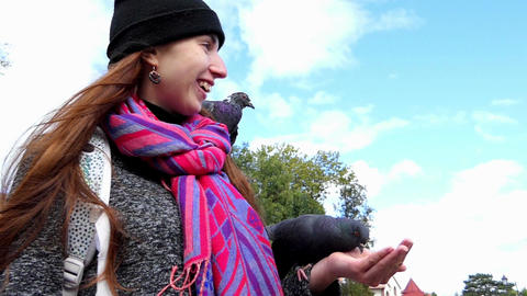 A young woman feeds doves from her hands in slo-mo Footage