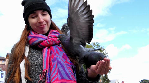 A young woman feeds pigeons from her hands in slo-mo Footage