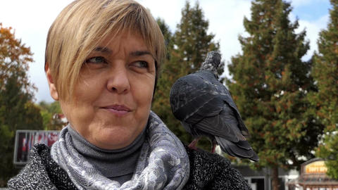 A cheery woman stands with a dove on her shoulder in slo-mo Footage