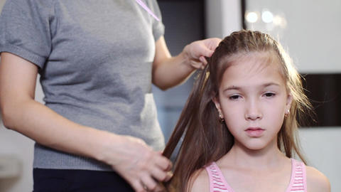 An attractive woman does her hairstyle for her little daughter. A woman is Footage