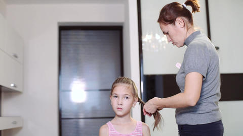 A pretty woman plaits the braid of her little daughter. Braiding the braids on Footage