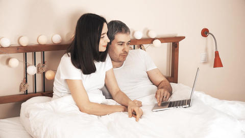 Happy couple shopping online using their laptop in bed at home Footage