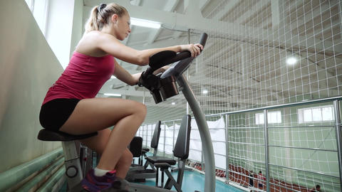 pretty girl is exercising on an exercise bike. The concept: to love sports, to Footage
