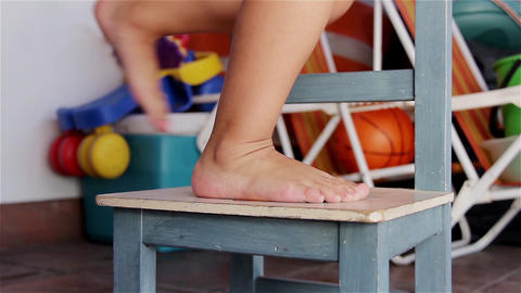 Girl climbing Barefoot a Chair in her Room 画像