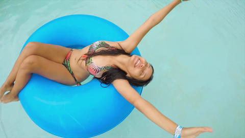 Young Happy Mixed Race Girl Relaxing in Swimming Pool with Rubber Ring. 4K 영상물