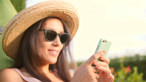 Relaxed Young Mixed Race Hipster Woman Looking at Mobile Phone in Hammock in Footage