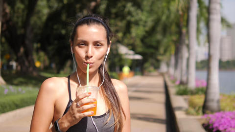 Attractive Mixed Race Yoga Girl Drinking Fresh Orange Juice after Workout in Footage