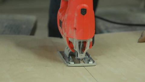 close-up, in the man's hand electric jig saw sawing a piece of plywood Footage