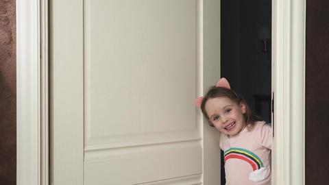 Cute little girl is looking from behind the door Footage