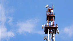 Telecommunication Tower With Antennas And Repeaters Against Blue Sky And Clouds Footage
