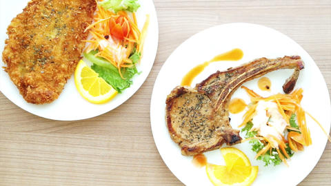 Battered fish steak and grilled pork chop steak with bone. colourful salad and v Footage