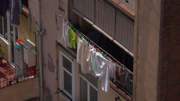 Bunch of clothes and linen dry hang out of loggia, telephoto view from above Live Action