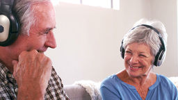 Mature couple listening to music with headphones on the couch Footage
