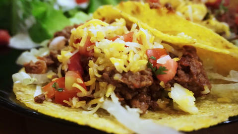 Soft Taco shells filled with mince meat, coriander and salsa on plate with salad Footage