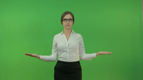 Young business woman raising her hands in different directions on a green Footage