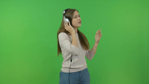 Beautiful girl with long hair listening to music through headphones. On the Footage