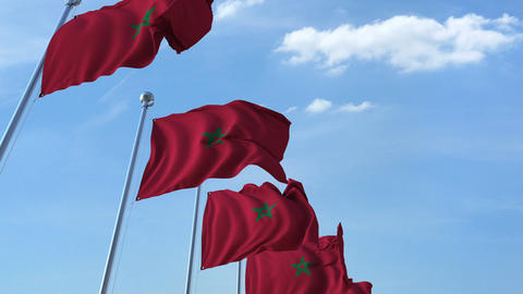 Multiple waving flags of Morocco against the blue sky Footage
