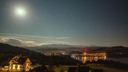 Night Time Lapse with Moon, Stars, Clouds, Mountains and Village near the Lake Footage