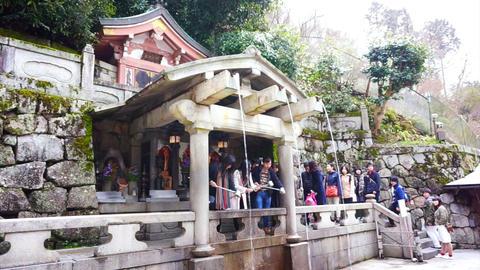 Kyoto, Japan - March 2015: people praying at spirit waterfall of ancient Kiyomiz Footage