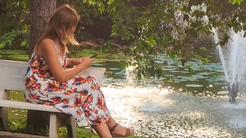 Blond Girl Sits on Bench at Pond Takes Photo with Iphone in Park Footage