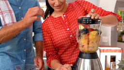 Couple preparing smoothie together Footage